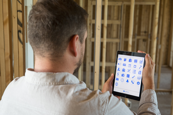 Contractor or project manager holding a tablet with software