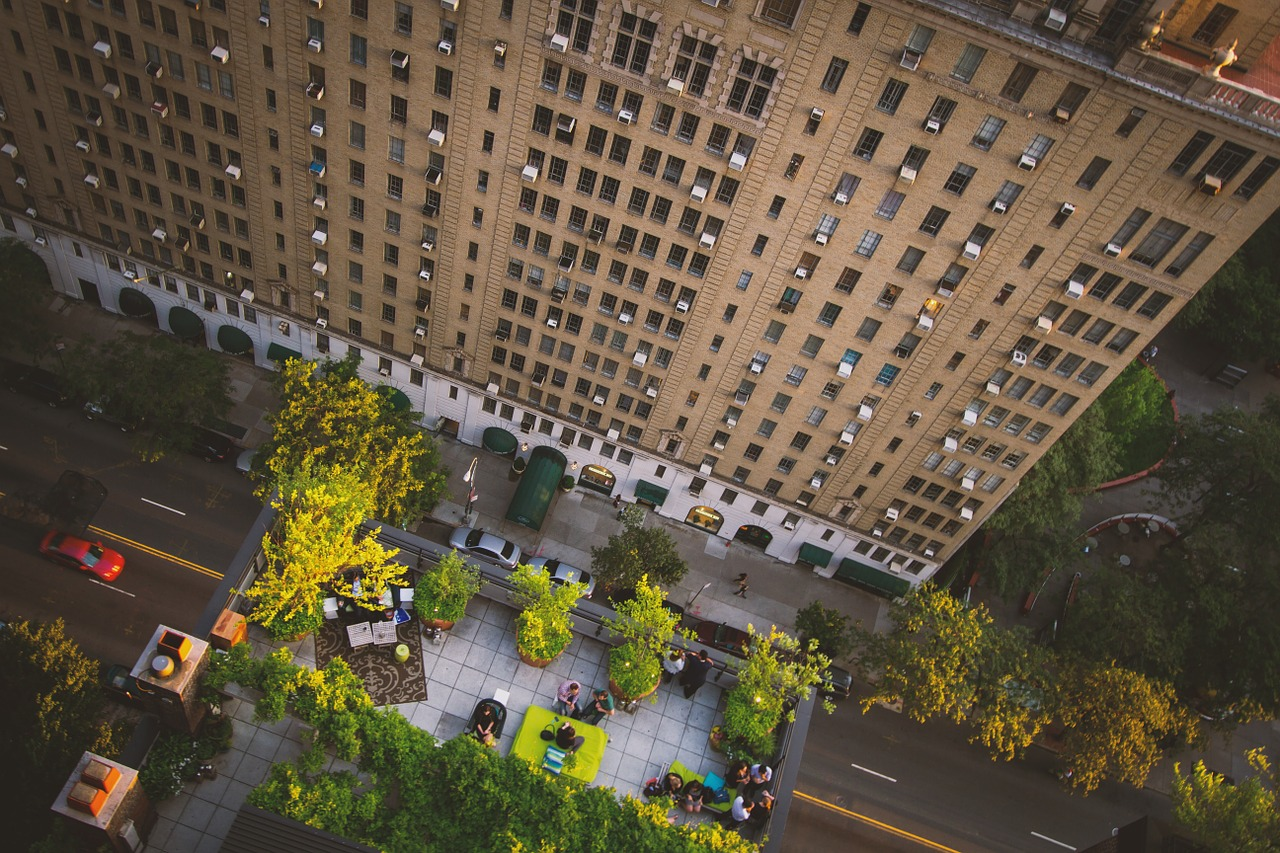 Rooftop view of a tall building looking down at greenery