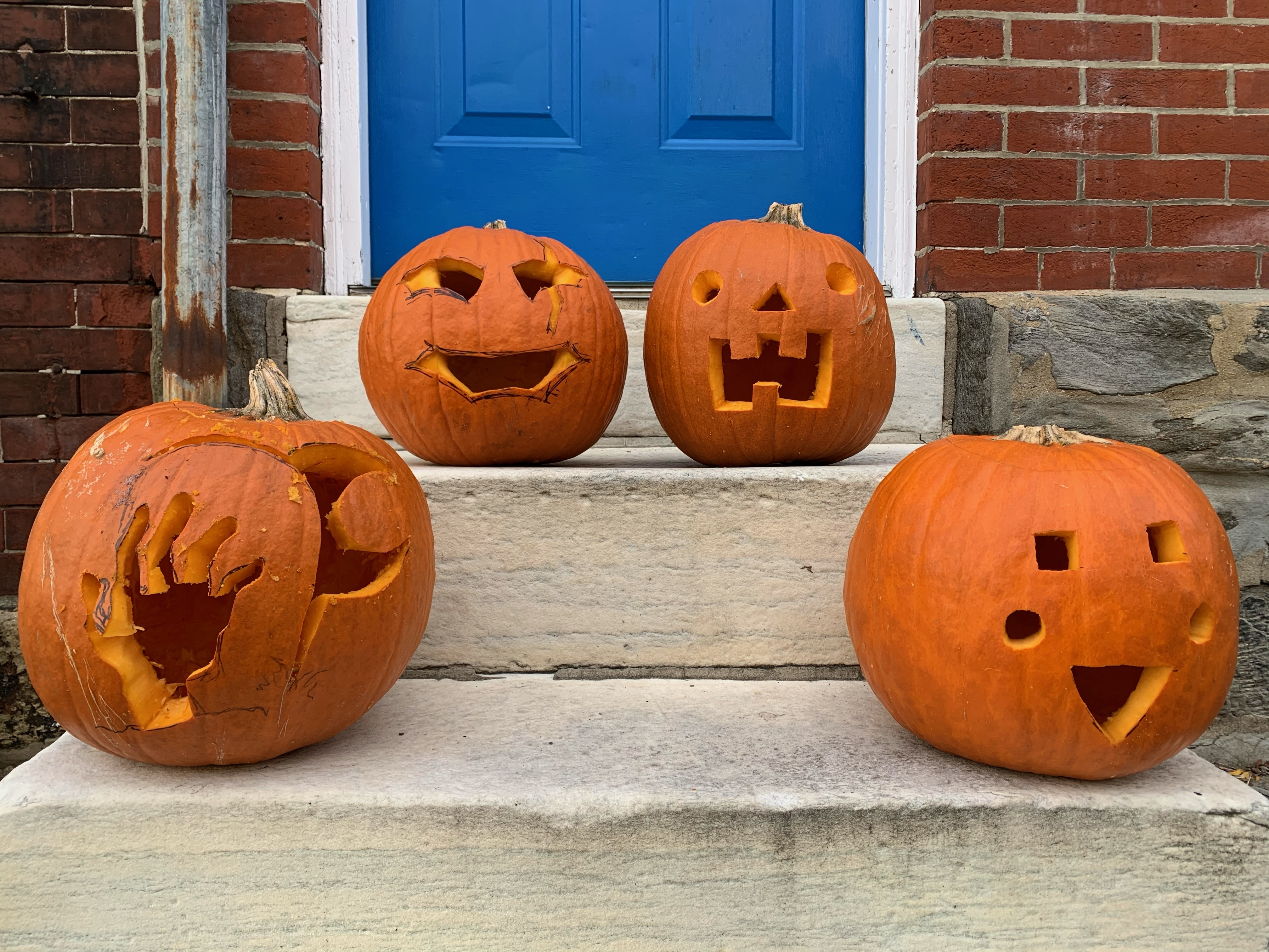 Four of the carved pumpkins sitting on a stoop