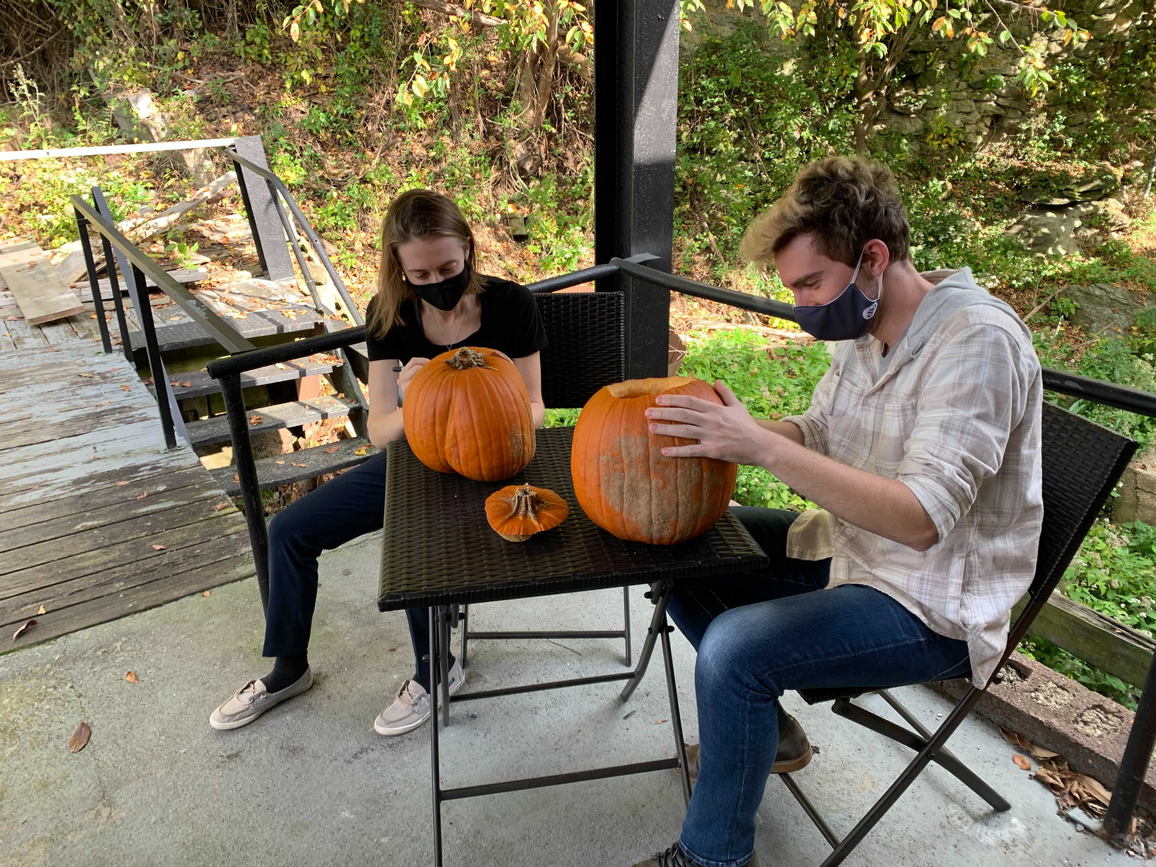 Two members of the visualization team sitting at a table to carve pumpkins