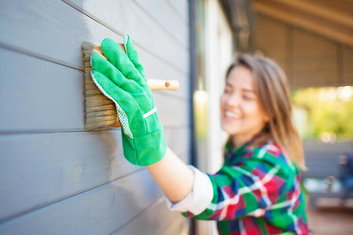 Woman with green gloves scrubbing her house's siding with a brush