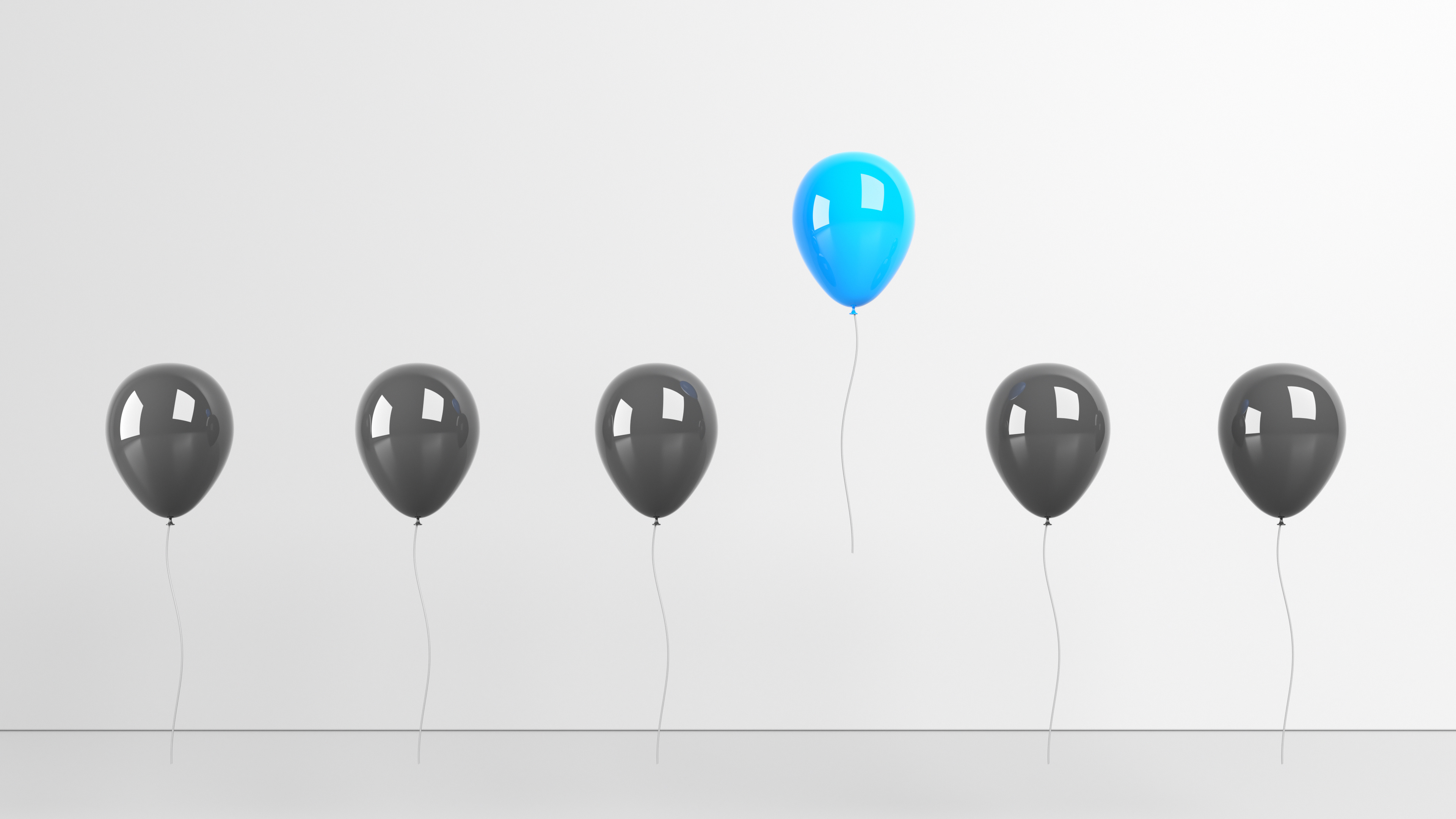 Solo blue balloon stands out from the other black balloons